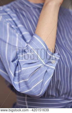A Beautiful Blue Shirt With A Thin Stripe On The Young Woman. A Womans Hand.