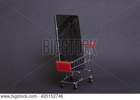 Belarus, Novopolotsk - 11 May, 2021: Phone Xiaomi In Shopping Cart On Black Background