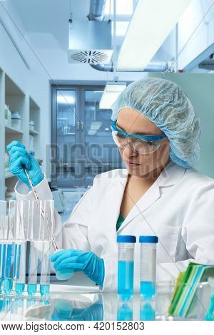 Pharma Female Tech Works In Laboratory. Caucasian Young Woman In Protective Gloves, Hat And White Go