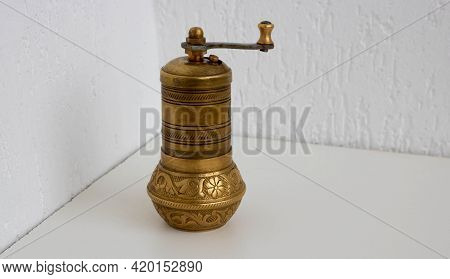 Old Bronze Bronze Coffee Grinder Stands On A White Background.
