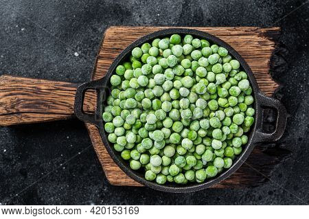 Fresh Frozen Green Peas In A Pan. Black Background. Top View