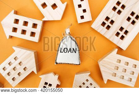 Money Bag With The Word Loan And Wooden Houses Around. The Concept Of Mortgage Housing And Real Esta