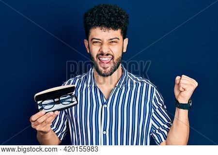 Young arab man with beard holding glasses in eyewear case screaming proud, celebrating victory and success very excited with raised arms