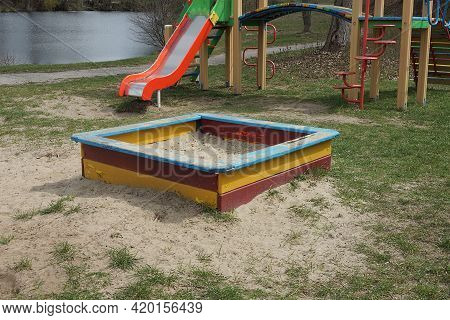 One Colored Square Wooden Sandbox With White Sand Stands On The Ground And Green Grass In The Playgr