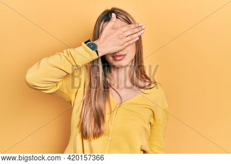 Beautiful hispanic woman wearing casual yellow sweater covering eyes with hand, looking serious and sad. sightless, hiding and rejection concept