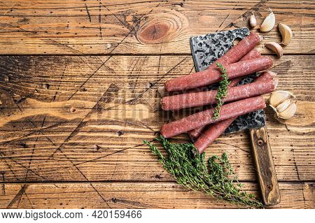 Uncooked Raw Beef And Pork Sausage On Vintage Meat Cleaver. Wooden Background. Top View. Copy Space