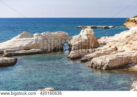 Bays And Bays Of Cyprus. Rocks With A Through Passage. Blue Waters Of The Lagoon With Caves And Rock