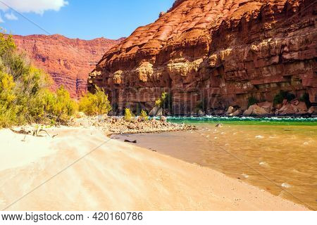 USA. Lee's Ferry is a historic boat ferry across the Colorado River. Stormy wide river with rapids and steep banks of red sandstone and cold water. The concept of active and photo tourism