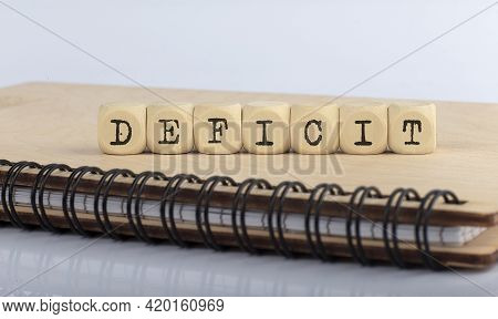 Deficit Word Written On The Wood Block On Wooden Notebook.top View Concept.