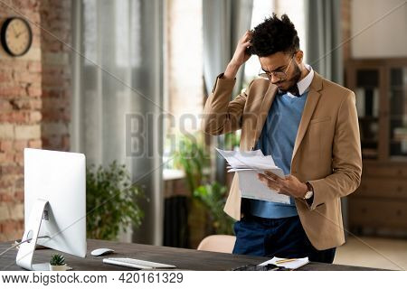 Confused young mixed race man in glasses and jacket standing at desk with computer and scratching head while reading papers