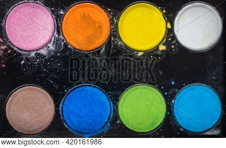 eight colors paints on black background