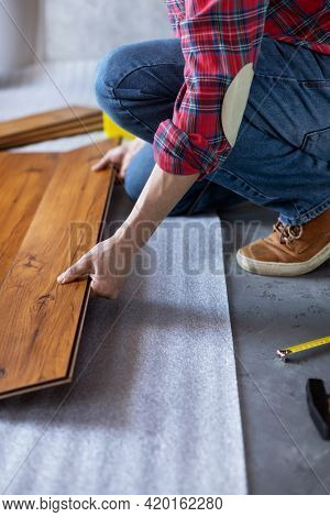 Man worker installing laminate flooring. Wooden laminate floor plank and tools with male hand