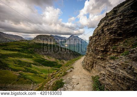 Trail Winds Around Cliff In Glacier National Park Along The Highline Trail