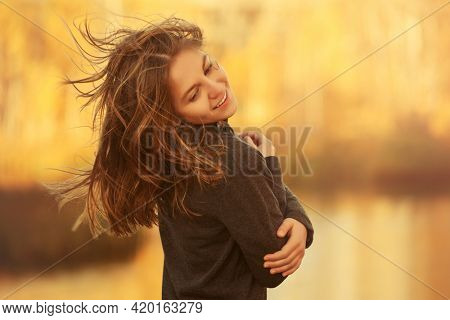 Happy young fashion girl in black pullover walking outdoor