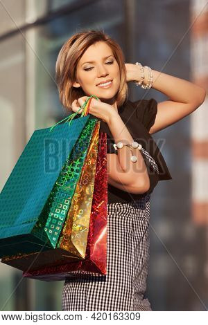 Happy young fashion woman with shopping bags walking on city street