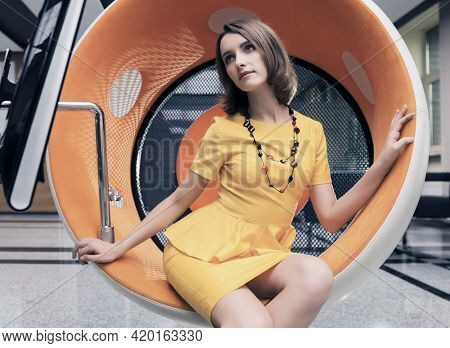 Young fashion business woman sitting on computer chair in office Stylish female model in yellow dress with bob hairstyle