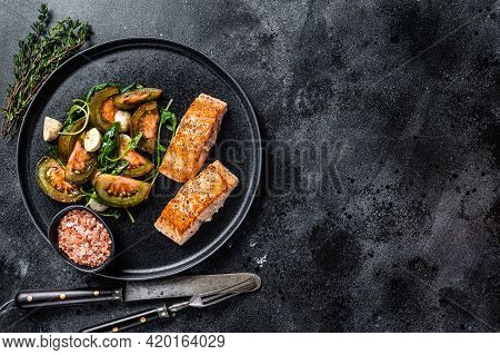 Fish Meal With Roasted Salmon Fillet Steaks And Arugula Tomato Salad On A Plate. Black Background. T