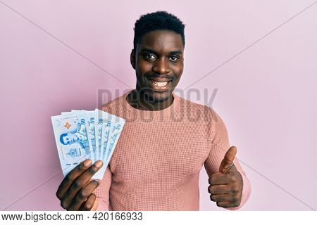 Handsome black man holding 50 thai baht banknotes smiling happy and positive, thumb up doing excellent and approval sign