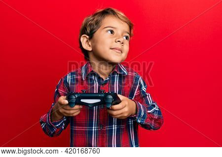 Adorable latin kid playing video game holding controller smiling looking to the side and staring away thinking.