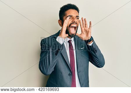 Handsome hispanic man with beard wearing business suit and tie shouting angry out loud with hands over mouth