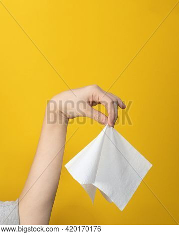 Close-up Of Hand Gesture Holding Napkin Neatly In Middle With Fingers On Yellow Background. Hand Dis