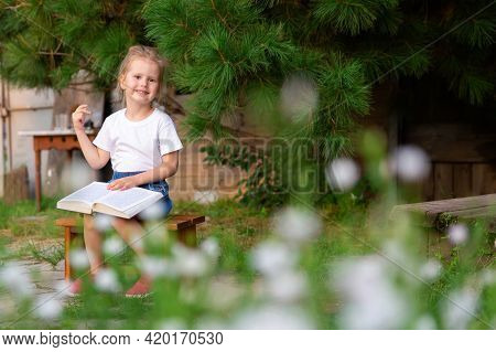 Child Sitting In The Backyard And Reading A Book. Carefree Childhood, Happy Child. Little Girl Readi