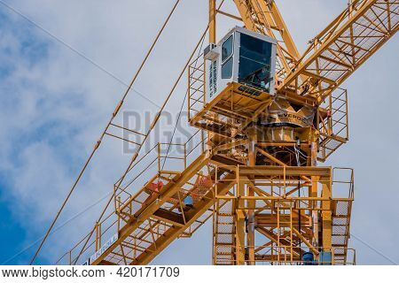Daejeon, South Korea; May 2, 2021: Closeup Of Operator Cab On Large Yellow Industrial Crane Against