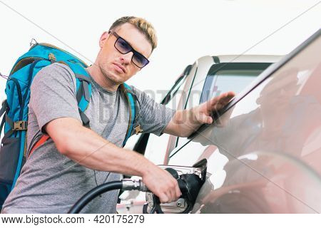 White Caucasian Car Owner With Blue Backpack Looking Straight, Holding Black Fuel Nozzle, And Fillin