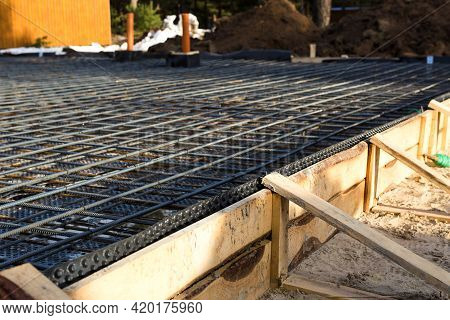 Iron Fittings On A Wooden Formwork With Laid Pipes Are The Basis For Pouring The Foundation Of The H