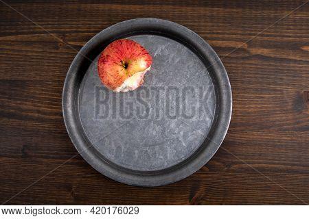 Bitten Apple On A Metal Plate. Dark Wood Texture Table