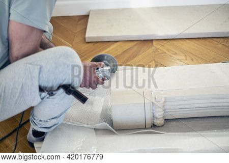 A Worker Cutting A Marble Column For Fireplace Wigth Electric Cutter, Indoor Closeup, Concept Of Saf