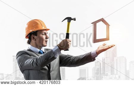 Businessman Going To Crash With Hammer House Symbol. Young Handsome Contractor In Business Suit And