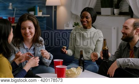 Multi-cultural Friends Laughing While Sharing Lifestyle Advice Sitting On Couch