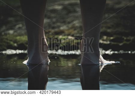 Barefoot In A Puddle. Woman Walks Barefoot In A Puddle Outdoors.