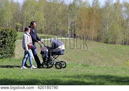 Moscow, Russia - May 2021: Couple With Baby Pram Walking In A Park. Family Leisure In Spring City