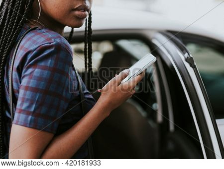 Black woman holding her phone while getting into a car