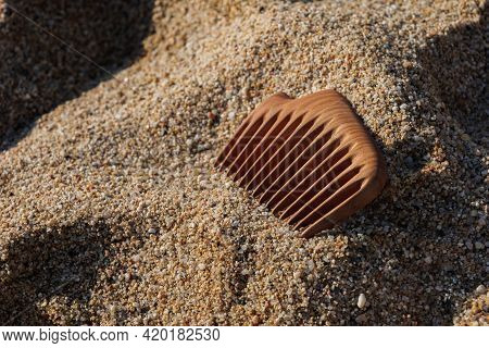 Handmade Wooden Comb On Sand At The Beach. Used For Head Massage And Combing. Hair Care Concept.