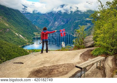 Female Tourist Enjoying Scenic View Over Fjord Geirangerfjorden From Flydalsjuvet Viewpoint, Holding