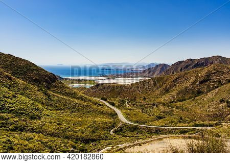 Spanish Mountains Landscape And View Of Sea Coast With Many Greenhouses In Valley. Winding Road To T