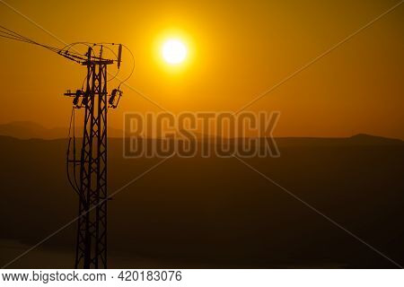 Coast With Electricity Transmission Pylons, Power Lines High Voltage Towers. Sunset Landscape.