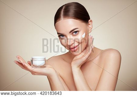Beauty Woman Applying Cream On Her Face. Young Woman With Clean Fresh Skin. Model With A Jar Of Face