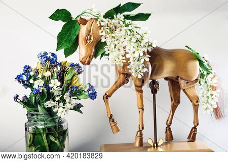 Wooden Articulated Dummy Horse Mannequin In White Inflorescences With A Small Bouquet Of Wild Flower