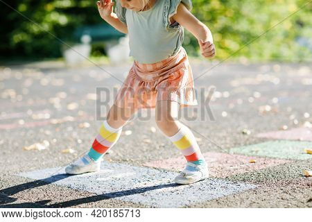 Closeup Of Leggs Of Little Toddler Girl Playing Hopscotch Game Drawn With Colorful Chalks On Asphalt