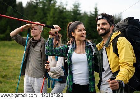 Trekking, Hiking, Camping And Wild Life Concept. Group Of Friends Walking Together In Nature
