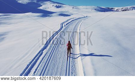 Cross Country Skier Traveling Across A Snow Covered Arctic Tundra In The High Mountains On A Cold Wi