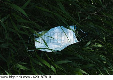 Used Medical Face Mask In The Green Grass. Biohazard, Microplastic, Post Covid Environmental Concern