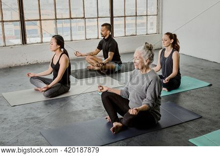 Diverse people meditating in a yoga class