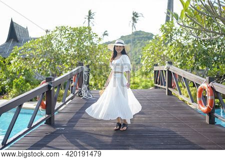 A Happy Beautiful Woman In White Dress Enjoying And Standing On Wooden Bridge Above Swimming Pool At