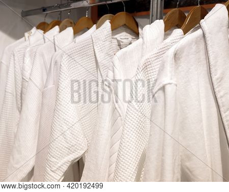 Various White Bathrobes Hang On Wooden Hangers In The Wardrobe.