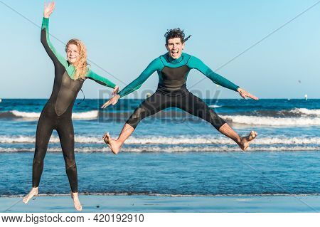Two Young Couple Jumping On Background Of Blue Sea. Outdoor Photo Of Gorgeous Happy Friends With Wet